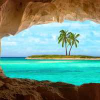 Viewing a tropical island and Palm tree through a cave