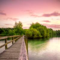Walkway across the water into the pink skies