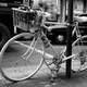 Black and White photo of Bicycle leaning on post