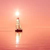 Boat sailing under the red sun on a lake