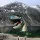 Dinosaur coming out of the lake with mountain in the background
