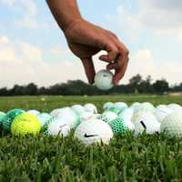 Hands placing golf balls