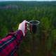 Holding a Cup over the forest