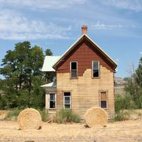 Wood House with hay Bales in front of it