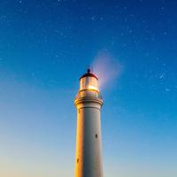 Lighthouse beneath the sky and stars with light on