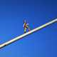 Man Figure walking towards sky on pole
