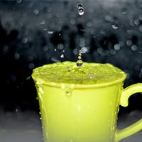 Raindrops falling in a cup