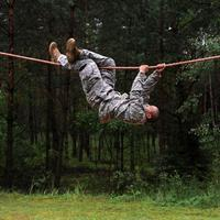 Army Soldier climbing upside down on the rope