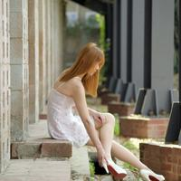 Asian Girl sitting on bricks in dress and high heels
