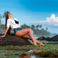 Attractive Woman lying on the rock near the seashore