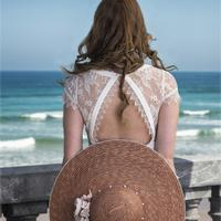 Back of Woman in dress and hat looking at the ocean