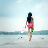 Back of woman wearing pink bathing suit walking down wooden dock