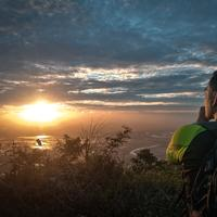 Backpacker on the mountain looking at sunset