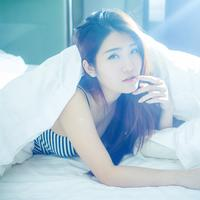 Beautiful Asian girl in bed in the sunlight