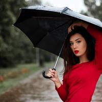 Beautiful Woman in red shirt and Umbrella in the rain