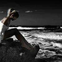 Beautiful Woman in white dress sitting on a rock by the ocean