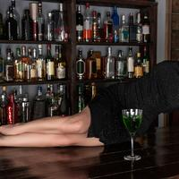 Beautiful Young Woman lying on a table with green drink in black dress