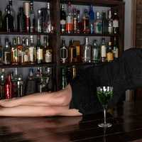 beautiful-young-woman-lying-on-a-table-with-green-drink-in-black-dress