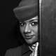 Black Woman wearing a hat behind a door