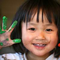 Child finger painting and smiling