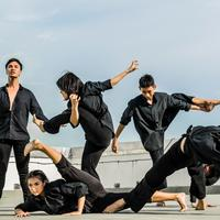 Dancing team in black doing a performance
