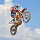 Dirt Biker jumping into air with motorcycle