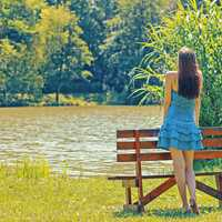girl-in-blue-dress-standing-by-a-bench-by-a-lake