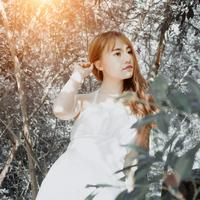 Girl in White Dress in the forest with light