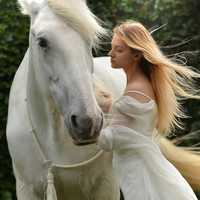 Girl in white dress with long hair with white horse