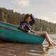 girl-sitting-in-canoe-with-feet-in-water-in-the-summer