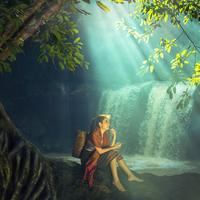 Girl sitting in the landscape besides a waterfall