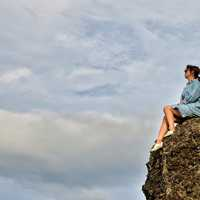 Girl sitting on a rock ledge