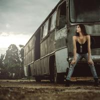 Girl sitting on broken down bus in black dress and jeans