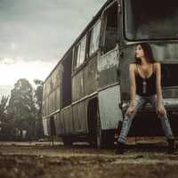 girl-sitting-on-broken-down-bus-in-black-dress-and-jeans