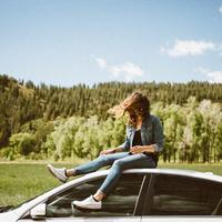 Girl sitting on Car with wind blowing through hair