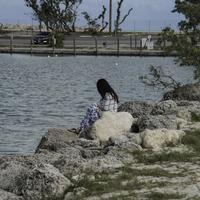 Girl sitting on the rocks of the shoreline