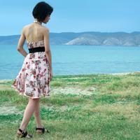 Girl walking on the shore in backless dress