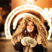 Girl with sparkler with light swirl in background in heavy coats