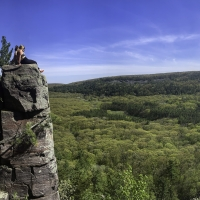 Girls sitting on a rock ledge Panoramic