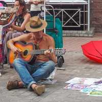 Guitar Player sitting down and street playing