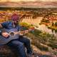 guitarist-playing-while-overlooking-city