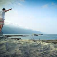 Guy standing on rock pretending to fly