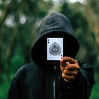 Hooded Guy holding up an ace of spades