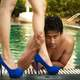 man-at-pool-holding-womens-legs