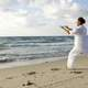 man-dressed-in-white-praticing-tai-chi-on-beasch
