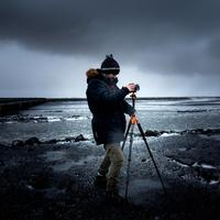 Man in Coat and Hat setting up Tripod on Beach under clouds