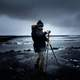 man-in-coat-and-hat-setting-up-tripod-on-beach-under-clouds