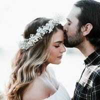 Man kissing girl with flower crown