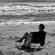 Man sitting on the beach monochrome