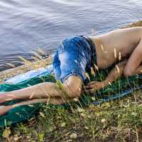 man-sleeping-on-the-riverbank